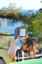 Young woman on hike resting on ground and reading ebook Royalty Free Stock Photo