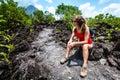 Woman hiker tying shoelace on mountain peak