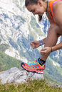 Young woman hiker  tying boot laces, high in the mountains Royalty Free Stock Photo