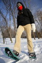 Young woman hiking with snowshoes / Rackets Stock Photo
