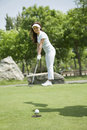 Young woman hitting the ball on the golf course women Stock Images