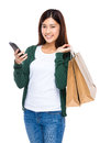 Young woman hold shopping bag and cellphone portrait isolated on white Royalty Free Stock Photo