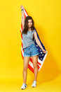 Young woman holding american flag full body vertical portrait of on yellow background in studio Stock Photos