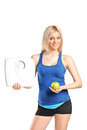 Young woman holding an apple and a weight scale attractive isolated on white background Royalty Free Stock Photo