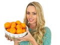 Young woman holding a basket of clementines dslr royalty free image an attractive healthy conscious smiling with long blonde hair Royalty Free Stock Image