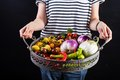 Young woman holding a basket full of veggies