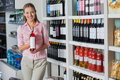 Young woman holding bottle of alcohol portrait beautiful at supermarket Stock Photography