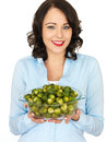 Young woman holding a bowl of brussels sprouts dslr royalty free image happy smiling with dark hair glass cooked healthy wearing Stock Photo