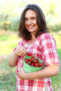 image photo : Young woman holding a bucket of strawberries outdoors