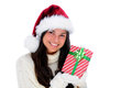 Young woman holding a christmas presents close to her face wrapped present the is looking towards the viewer and smiling she is Royalty Free Stock Photo