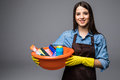 Young woman holding cleaning tools and products in bucket, isolated on grey Royalty Free Stock Photo