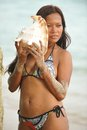 Young woman holding a conch shell on the beach to her ears Stock Photos