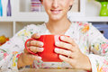 Young woman holding cup of coffee a big red Stock Photo