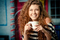 Young woman holding cup of coffee outside cafe Royalty Free Stock Photo
