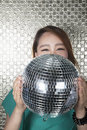 Young woman holding a disco ball looking at camera in front of shiny wall women Royalty Free Stock Photos