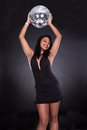 Young woman holding disco ball over black background Royalty Free Stock Images