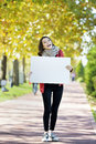 Young woman holding empyt billboard happy walking in autumn park looking at camera and empty hands Stock Images