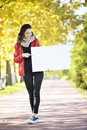 Young woman holding empyt billboard happy walking in autumn park looking at and empty board hands Royalty Free Stock Image