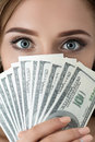 Young woman holding fan of hundred dollar bills portrait eyes close up shot Stock Photography