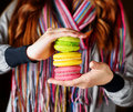 Young woman holding the french pastry macaron in cafe Stock Photo
