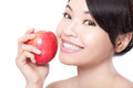 Young woman holding a fresh ripe apple portrait of lovely and smiling with health teeth isolated on white background asian beauty Royalty Free Stock Photo