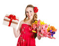 Young woman holding gift box and flowers. Royalty Free Stock Photography