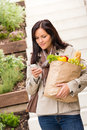 Young woman holding groceries vegetables shopping phone Royalty Free Stock Photo