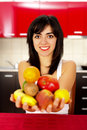 Young woman holding a handful fruits in the kitchen smiling Royalty Free Stock Photo