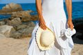 Young woman holding hat and flip flops on beach. Royalty Free Stock Photo