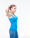 Young woman holding her hair in a ponytail isolated on white background wearing blue t shirt and jeans looking away Royalty Free Stock Images