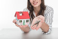 Young woman holding house model with keys and smiling at camera Royalty Free Stock Photo