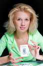 Young woman holding a joker card in hand Royalty Free Stock Photo