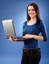 Young woman holding a laptop portrait of on blue background Royalty Free Stock Images