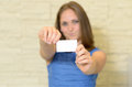 Young woman holding out a business card Royalty Free Stock Photo