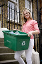 A young woman holding a recycling box, on her doorstep Royalty Free Stock Photo