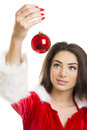 Young woman holding red christmas ball beautiful delighted in santa claus outfit up a against white background selective focus on Royalty Free Stock Photos