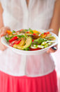 Young woman holding salad plate in summer wear colourful Royalty Free Stock Images