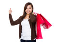 Young woman holding with shopping bag and thumb up