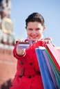 Young woman holding shopping bags and showing credit card in front of spasskaya tower Stock Photos