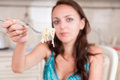 Young woman holding up forkful of spaghetti pasta brunette to camera close noodles twirled around fork tines with hungry Stock Photography
