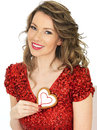 Young woman holding valentines ginger biscuits a dslr royalty free image of an attractive with dark blonde hair a biscuit heart Stock Photos