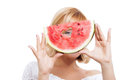 Young woman holding watermelon looking through slice of Stock Image