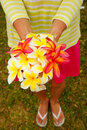 Young woman holding white and pink plumeria flowers in her hands Royalty Free Stock Images