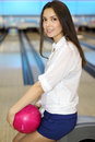 Young woman holds ball and sits in bowling club Royalty Free Stock Photo