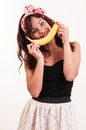 Young woman holds up a banana to her mouth imitating a smile on Stock Images