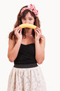 Young woman holds up a banana to her mouth show an sad face Stock Photography