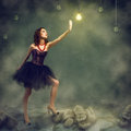 Young woman holds up a hand to a glowing light bulb Royalty Free Stock Photo