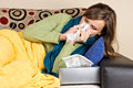 Young woman at home having flu blowing her nose Stock Image