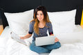Young woman in Hotel in bed with wifi and computer Royalty Free Stock Photo