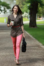 Young woman in a hurry holding cup of coffee walking outside park Royalty Free Stock Photos